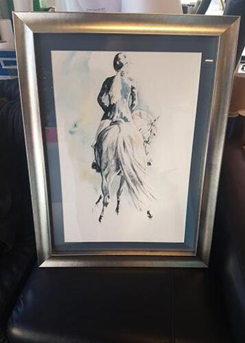 Painting of horse and rider with silver frame.
